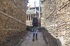 Jonge Mooie Vrouw die Rode Jasjerugzak dragen die Bergendorp kruisen De Rotsenweg van de bergtrekking Oude Stad Royalty-vrije Stock Fotografie