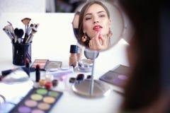 Jonge mooie vrouw die samenstelling maken dichtbij spiegel, die bij het bureau zitten Royalty-vrije Stock Afbeeldingen