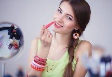 Jonge mooie vrouw die samenstelling maken dichtbij spiegel, die bij het bureau zitten Stock Foto's
