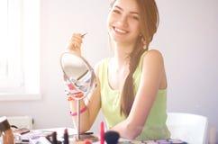 Jonge mooie vrouw die samenstelling maken dichtbij spiegel, die bij het bureau zitten Royalty-vrije Stock Foto