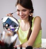 Jonge mooie vrouw die samenstelling maken dichtbij spiegel, die bij het bureau zitten Stock Foto
