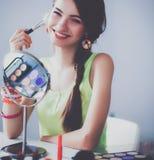 Jonge mooie vrouw die samenstelling maken dichtbij spiegel, die bij het bureau zitten Royalty-vrije Stock Fotografie