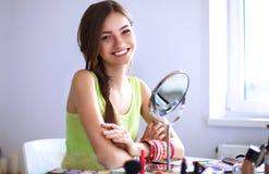 Jonge mooie vrouw die samenstelling maken dichtbij spiegel, die bij het bureau zitten Stock Afbeelding