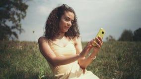 Jonge mooie vrouw die selfie op telefoon nemen terwijl het zitten op gras stock footage