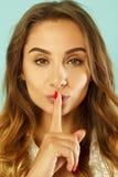Jonge mooie vrouw die shh gebaar over blauwe achtergrond zeggen stock fotografie
