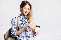 Jonge mooie vrouw die slimme telefoon met behulp van Royalty-vrije Stock Foto