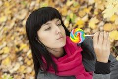 Jonge mooie vrouw die suikergoedlollys eet Royalty-vrije Stock Fotografie