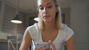 Jonge mooie vrouw die telefoon thuis met behulp van stock footage