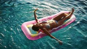 Jonge mooie vrouw die van de zomer op opblaasbare matras in glashelder water in een zwembad genieten tijdens zonsondergangtijd stock video
