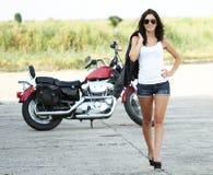 Jonge mooie vrouw die van een motorfiets loopt royalty-vrije stock afbeelding