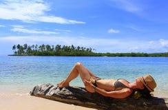 Jonge mooie vrouw die van haar tijd genieten en dicht bij het overzees rusten Royalty-vrije Stock Foto's