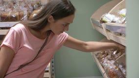 Jonge mooie vrouw die vers brood in een supermarkt kopen stock footage