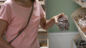 Jonge mooie vrouw die vers brood in een supermarkt kopen stock video