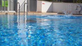 Jonge mooie vrouw die in water van bassin op zonnige dag springen Donkerbruin meisje die in pool zwemmen en op zonnige dag ontspa stock videobeelden