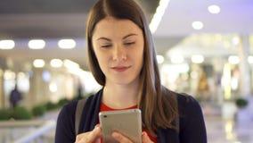 Jonge mooie vrouw die in winkelcomplex het glimlachen lopen Het gebruiken van haar smartphone, die met vrienden spreken stock footage