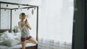 Jonge mooie vrouw die yogaoefening thuis doen dichtbij bed in slaapkamer Royalty-vrije Stock Foto's
