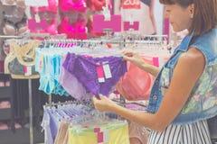 Jonge mooie vrouw die, zich bevindt in de wandelgalerij, kiezend nieuwe lilac ondergoeddamesslipjes, bekijkend aan stof of prijs  Royalty-vrije Stock Foto