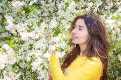 Jonge mooie vrouw die zich dichtbij boom met bloemen bevinden Royalty-vrije Stock Afbeelding