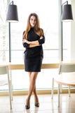 Jonge mooie vrouw die zich dichtbij lijst in bureauruimte bevinden royalty-vrije stock foto