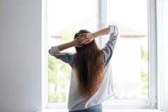 Jonge mooie vrouw die zich dichtbij venster bevinden Royalty-vrije Stock Foto