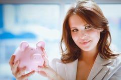 Jonge mooie vrouw die zich met die de spaarpot van het spaarvarken bevinden, op witte achtergrond wordt geïsoleerd Stock Fotografie