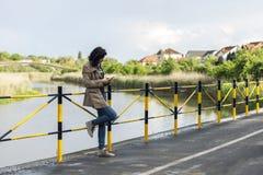Jonge mooie vrouw die zich naast het meer texting bericht bevinden stock fotografie