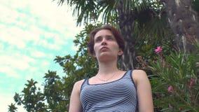 Jonge mooie vrouw die zich op dijk onder palm bevinden die retro zwempak met blauwe en witte strepen dragen stock footage