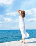Jonge mooie vrouw die zich op een pijler bij de zomer bevinden Vakantie, t royalty-vrije stock afbeelding