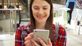 Jonge mooie vrouw die zich in winkelcomplex het glimlachen bevinden Het gebruiken van haar smartphone, die met vrienden spreken stock videobeelden