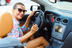 Jonge mooie vrouw die in zonnebril in een convertibele autowi zitten Stock Afbeeldingen