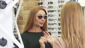 Jonge mooie vrouw die zonnebril proberen die met haar vriend winkelen stock footage