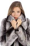 Jonge mooie vrouw in een bontjas in profiel stock foto