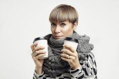 Jonge mooie vrouw in een grijze uitrusting die een koffie van document koppen hebben De meeneemlay-out van het pakketontwerp Stock Foto