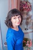 Jonge mooie vrouw in een nauwsluitende kleding in Kerstmisbinnenland Stock Foto