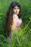 Jonge mooie vrouw in groen gras Stock Afbeeldingen
