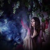 Jonge mooie vrouw in het beeld van feeën, magisch donker bos Stock Fotografie