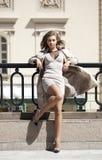 Jonge mooie vrouw in het beige laag stellen in openlucht in zonnige wea Stock Afbeeldingen