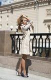 Jonge mooie vrouw in het beige laag stellen in openlucht in zonnige wea Stock Foto