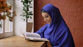 Jonge mooie vrouw in het blauwe boek van de hijablezing en zitting in koffie, charmante dame met doordrongen neus stock footage