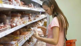 Jonge mooie vrouw het kopen worst bij koelkastsectie in supermarkt Royalty-vrije Stock Afbeeldingen