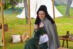 Jonge mooie vrouw in het middeleeuwse kostuum naaien. Stock Foto's