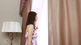 Jonge mooie vrouw het openen gordijnen in een slaapkamer stock videobeelden