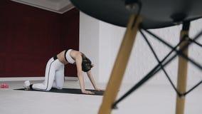 Jonge mooie vrouw het praktizeren yoga binnen op de witte en rode achtergrond Wellnessconcept De kalmte en ontspant stock footage