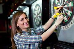 Jonge mooie vrouw het spelen pijltjes in een club stock fotografie
