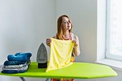 Jonge mooie vrouw het strijken kleren Stock Foto