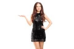 Jonge mooie vrouw in het zwarte elegante kleding gesturing Stock Foto's