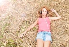 Jonge mooie vrouw in hoofdtelefoons op hooi. Stock Foto