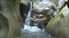 Jonge mooie vrouw in langzame motie die duidelijk water van bergmeer en blikken bespatten aan camera met kleine binnen waterval stock footage