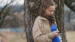 Jonge mooie vrouw in lichtbruine uitstekende retro laag die haar smartphone op plattelandslandschap gebruiken stock footage