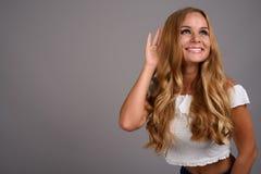 Jonge mooie vrouw met blond haar tegen grijze achtergrond royalty-vrije stock foto